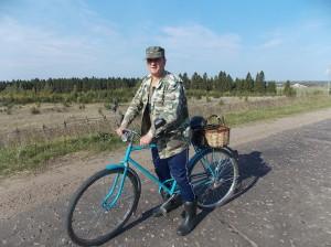 Быстро катит на велосипеде местный житель — держит путь в деревню Ежово.